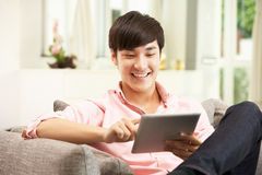 Homem chinês novo que usa a tabuleta de Digitas Imagem de Stock Royalty Free