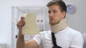 Homem chocado no estilingue do braço e no colar cervical que olham a conta médica, extensões filme
