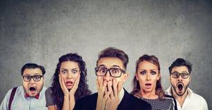 Homem chocado nos vidros e em seus amigos assustado imagem de stock