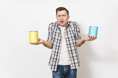 Homem chocado novo na roupa ocasional que guarda latas de lata vazias da pintura com o espaço da cópia isolado no fundo branco imagens de stock