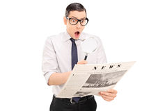 Homem chocado que lê a notícia através de uma lente de aumento Foto de Stock Royalty Free