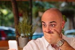 Homem chocado que olha seu telefone imagem de stock