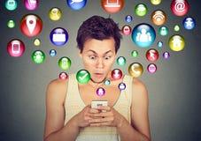Homem chocado que usa os ícones da aplicação do smartphone que voam fora do telefone celular Imagens de Stock Royalty Free