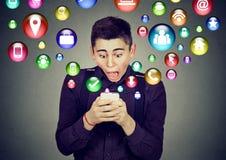 Homem chocado que usa os ícones da aplicação do smartphone que voam fora do telefone celular Fotografia de Stock