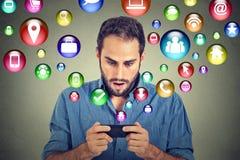 Homem chocado que usa texting nos ícones da aplicação do smartphone que voam fora do telefone celular Imagem de Stock