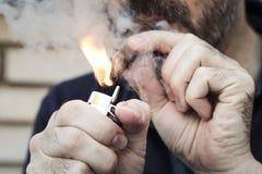 Homem coberto no charuto da iluminação do fumo com um isqueiro do metal fotografia de stock royalty free