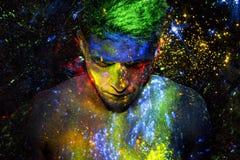 Homem coberto no pó colorido de incandescência fotos de stock royalty free