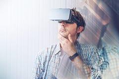 Homem com óculos de proteção de VR que explora o índice da realidade virtual imagens de stock royalty free
