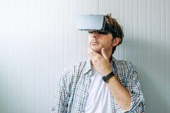 Homem com óculos de proteção de VR que explora o econtent da realidade virtual imagem de stock royalty free