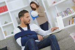 Homem com apoio do estilingue do braço usando o portátil Imagem de Stock Royalty Free