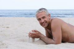 Homem com a areia nas mãos Fotos de Stock Royalty Free