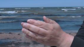 Homem com a areia nas mãos na praia pelo mar filme