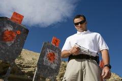 Homem com a arma da mão perto dos alvos na escala de acendimento Imagem de Stock