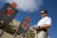 Homem com a arma da mão perto dos alvos na escala de acendimento Imagem de Stock Royalty Free