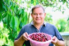 Homem com as cerejas no jardim fotografia de stock royalty free