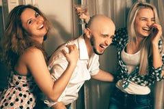 Homem com as duas meninas encantadores que riem de um partido Imagem de Stock