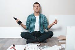 Homem com as ferramentas nas mãos que sentam-se no assoalho no estado de harmonia fotografia de stock royalty free