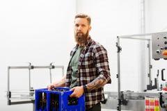 Homem com as garrafas na caixa na cervejaria da cerveja do ofício foto de stock royalty free