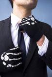 Homem com as luvas de esqueleto que ajustam o seu laço Foto de Stock Royalty Free