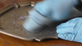 Homem com as luvas que lustram uma bandeja de prata antiga video estoque