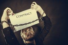 Homem com as mãos acorrentadas que guardam o contrato Imagem de Stock Royalty Free