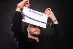 Homem com as mãos acorrentadas que guardam o contrato Fotos de Stock