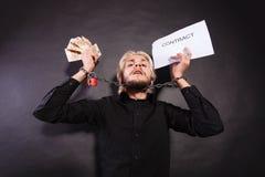 Homem com as mãos acorrentadas que guardam o contrato e o dinheiro Fotografia de Stock