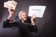 Homem com as mãos acorrentadas que guardam o contrato e o dinheiro Imagens de Stock