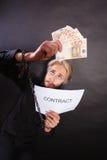 Homem com as mãos acorrentadas que guardam o contrato e o dinheiro Fotografia de Stock Royalty Free