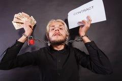 Homem com as mãos acorrentadas que guardam o contrato e o dinheiro Fotos de Stock Royalty Free