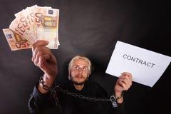 Homem com as mãos acorrentadas que guardam o contrato e o dinheiro Imagens de Stock Royalty Free