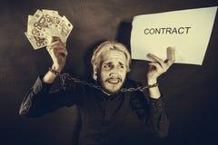 Homem com as mãos acorrentadas que guardam o contrato e o dinheiro Fotos de Stock