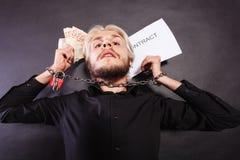 Homem com as mãos acorrentadas que guardam o contrato e o dinheiro Foto de Stock