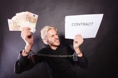 Homem com as mãos acorrentadas que guardam o contrato e o dinheiro Foto de Stock Royalty Free