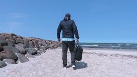 Homem com as mãos que estão acima apenas na praia perto do mar vídeos de arquivo