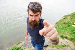 Homem com barba e bigode com óculos de sol, beira-rio no fundo Conceito apontar e de sentido Moderno em sério imagem de stock