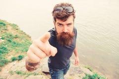 Homem com barba e bigode com óculos de sol, beira-rio no fundo Conceito apontar e de sentido Moderno em sério fotos de stock