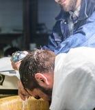 Homem com barba e bigode com a toalha nos ombros, mãos masculinas com o chuveiro no fundo Cliente farpado do homem do moderno Fotografia de Stock