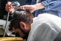 Homem com barba e bigode com a toalha nos ombros, mãos masculinas com o chuveiro no fundo Cliente farpado do homem do moderno Fotos de Stock