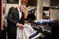 Homem com a barba que escolhe a camisa em uma loja Imagem de Stock