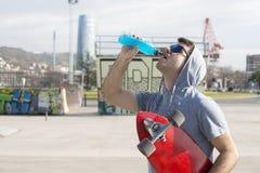 Homem com bebida bebendo da energia do skate após o esporte. foto de stock