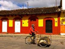 Homem com a bicicleta da entrega na frente das casas coloniais coloridas em San Cristobal de Las Casas Imagens de Stock