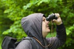 Homem com binóculos que olha pássaros no parque Foto de Stock