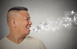 Homem com a boca aberta que funde os flocos de neve frios da brisa que voam afastado Fotografia de Stock