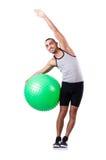 Homem com a bola suíça que faz exercícios Foto de Stock