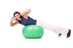 Homem com a bola suíça que faz exercícios Fotografia de Stock