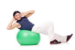 Homem com a bola suíça que faz exercícios Fotografia de Stock Royalty Free