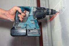 Homem com a broca de mão sem corda que fura um furo no concreto com nível do laser fotos de stock royalty free