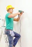 Homem com a broca elétrica que faz o furo na parede Fotografia de Stock Royalty Free