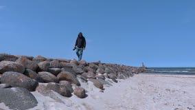 Homem com a câmera da foto no cais de pedra pelo mar vídeos de arquivo